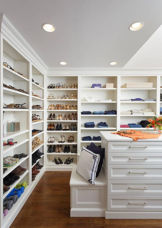 Custom Walk In Closet Features Walls Lined With Floor To Ceiling White Modular Shoe And Jean Shelves Lit By Recessed Lighting Facing A Island