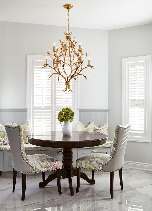 Your Eyes Can T Help But Be Drawn To A Stunning Gold Leaf Chandelier Hung Above A Dark Stained Round Dining Table Seating Green And Pink Floral Dining