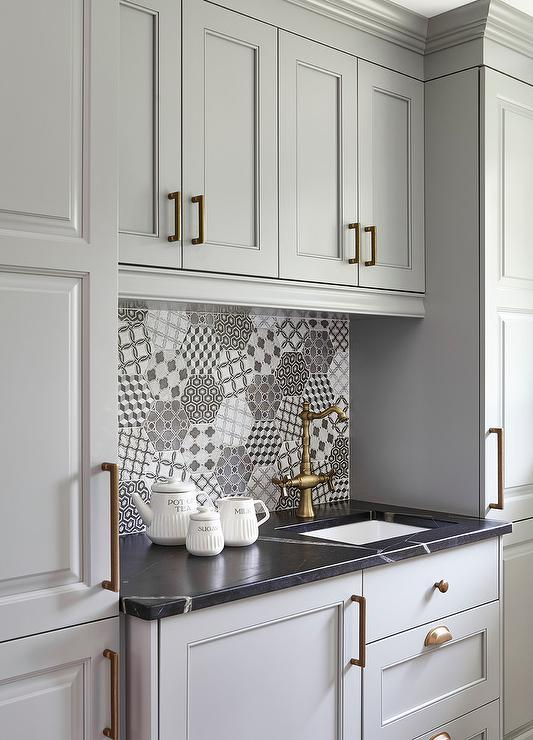 Gray Kitchen Pantry Cabinets Accented With Brushed Brass Hardware Flanks Raised Panel Topped A Honed Black Marble Countertop Fitted