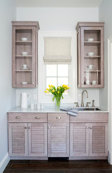 chic butlers pantry features gray wash oak cabinets upper cabinets with glass front doors and lower cabinets with louvered doors paired with honed white