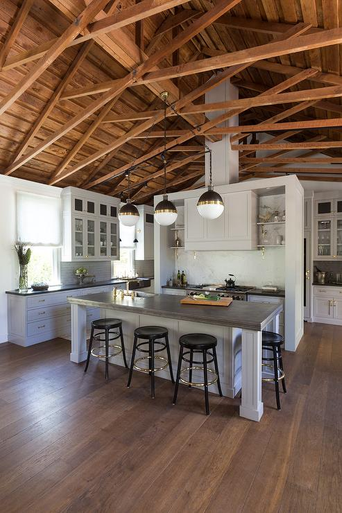 fabulous kitchen features a truss ceiling accented with three small hicks pendants illuminating a pale gray center island topped with antique pewter fitted