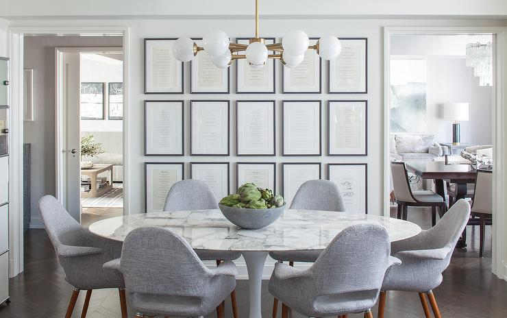 A white glass and brass globe chandelier hangs over a Saarinen Oval Dining  Table surrounded by 6 Saarinen Executive Armchairs with Wood Legs placed in  front. White Glass And Brass Globe Dining Room Chandelier Design Ideas