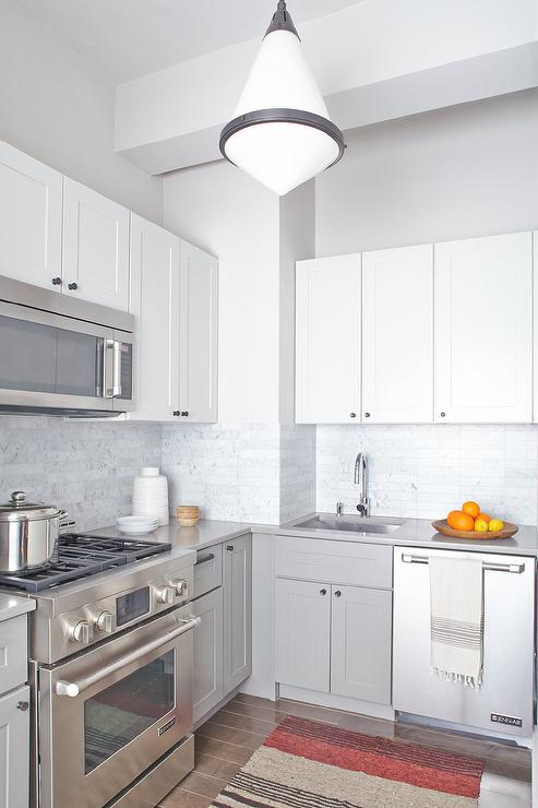 Small Two Toned White And Gray Kitchen Features A Gale Petite Pendant Light  Hung Over A Brown And Orange Rug Placed In Front Of A Stainless Steel Oven  Range ...
