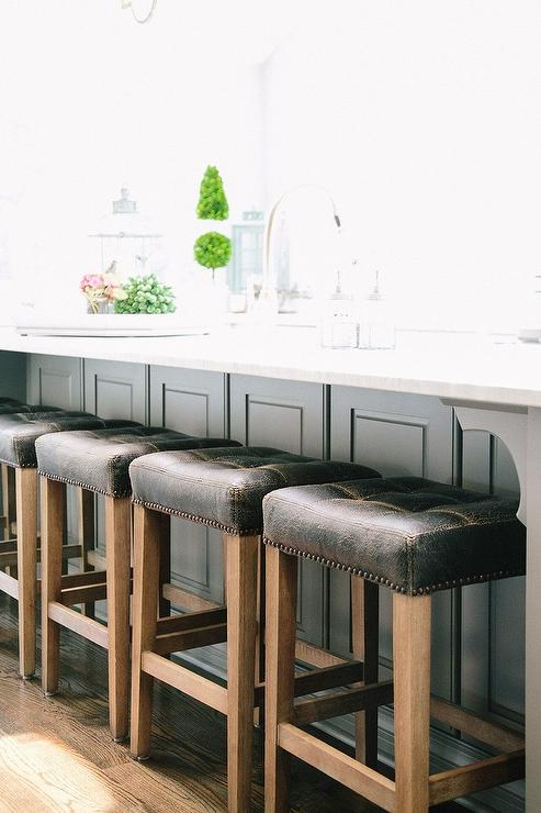 Fabulous kitchen features a gray wainscoted center island topped with white quartz fitted with a farm sink lined with backless black leather tufted counter ... : backless kitchen counter stools - islam-shia.org