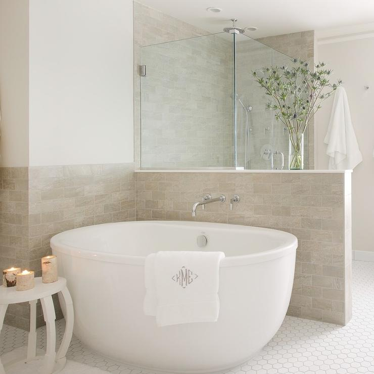 restful bathroom is equipped with a white oval tub placed on white hex floor tiles beside a white side table and against light taupe wall tiles - Pony Wall