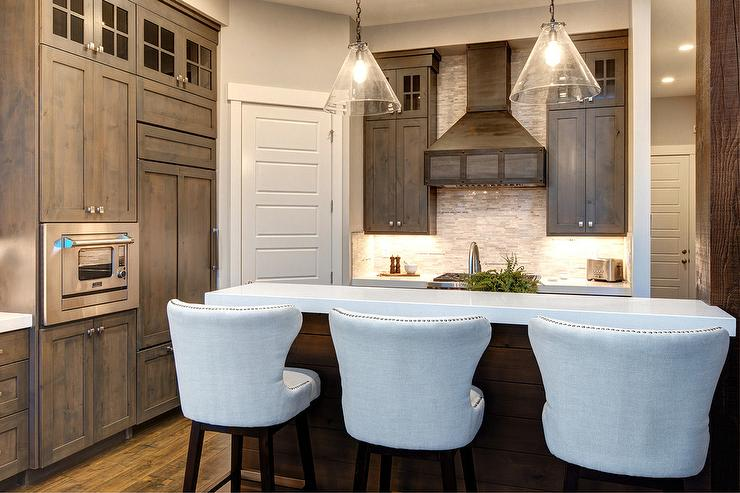 Brown Stained Kitchen Cabinets With White Quartz Countertop
