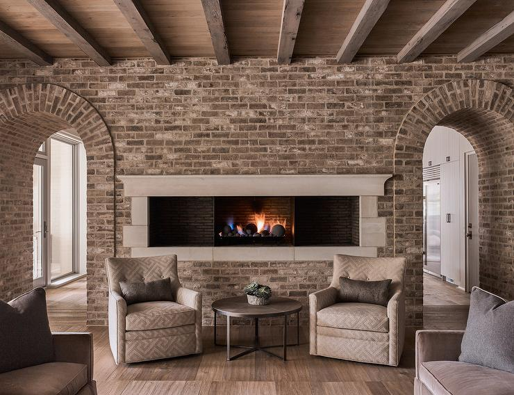 Gorgeous cottage living room boasts a stunning plank ceiling accented with wood beams and gray brick framing arched doorways and a long narrow fireplace fixed to the wall behind gray Greek key chairs topped with gray pillows and placed flanking a round wo