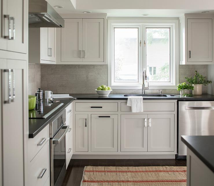 Chic Kitchen Features Extra Light Gray Cabinets Paired With Black Quartz Countertops And A Linear Tile Backsplash