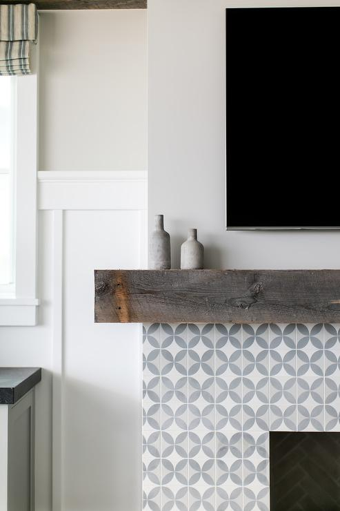 A flat panel television is mounted above a chunky rustic wood fireplace mantle accenting a white and gray cement tiled fireplace finished with a herringbone tiled firebox.