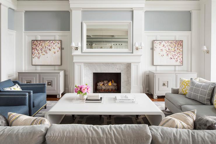 White and gray living room features two gray sofas and a pair of blue accent chairs facing a white lacquered waterfall coffee table placed atop a gray