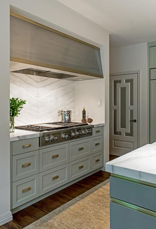 An Eye Catching Stainless Steel Hood With A Gold Trim Is Mounted In A  Cooking Nook Above A Stainless Steel Cooktop Fixed Against A Bookmatched  Marble ...