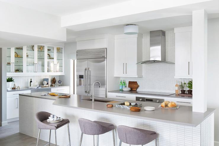Welcoming Gray And White Contemporary Kitchen Features Modern Gray Linen Barstools Placed In Front Of A White Grid Tiled Island Topped With A Light Gray