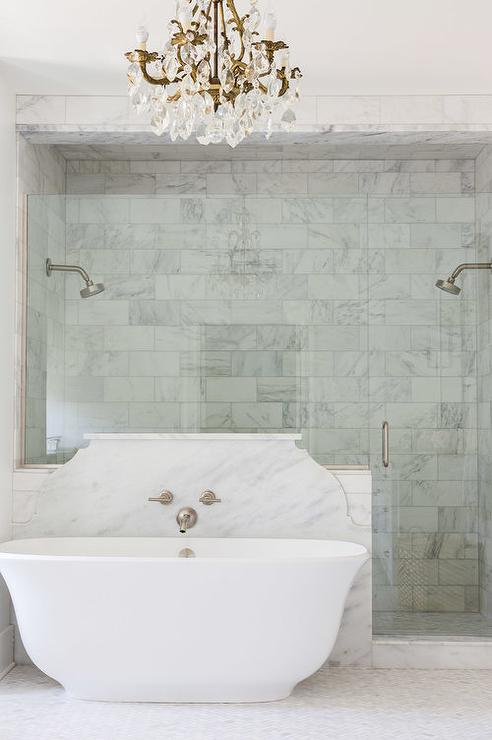 Alyssa Rosenheck Laurel Powell An Oval Bathtub Stands In Front Of A Curved Marble Backsplash Placed Next To A Seamless Glass Door Which Leads Into A