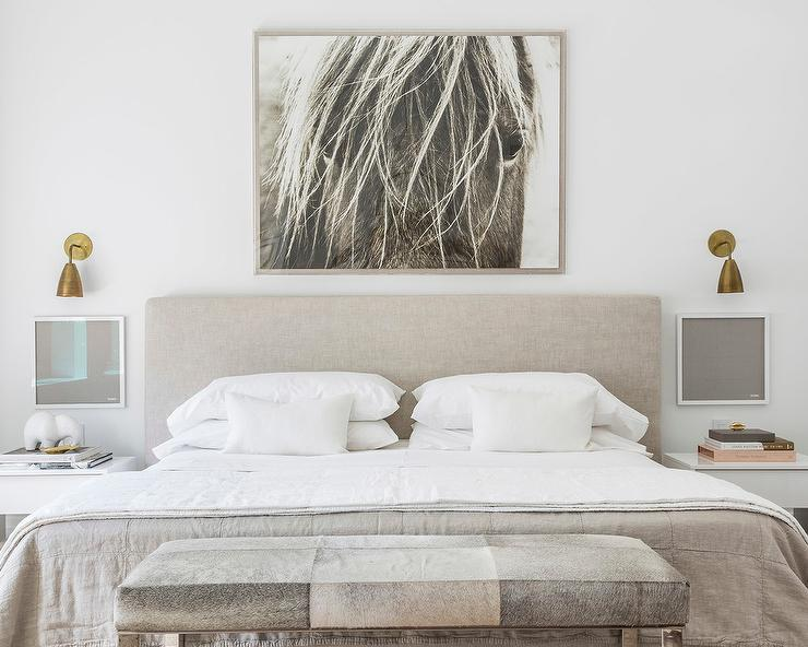 Restful gray bedroom boasts a black and white horse art piece mounted to a white wall above a gray headboard accenting a bed dressed in gray and white