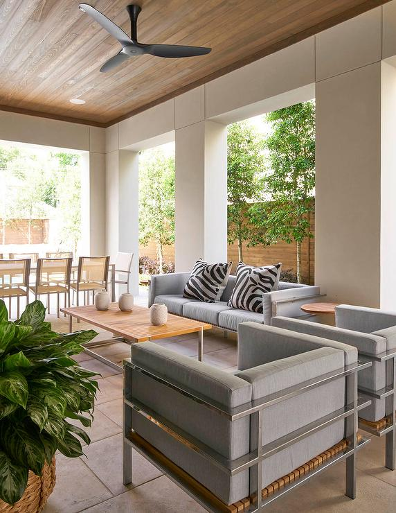 A Modern Black Ceiling Fan Is Mounted To A Rustic Covered Patio Ceiling  Above A Teak Slat Top Coffee Table Seating A Modern Gray Sofa Topped With  Black And ...