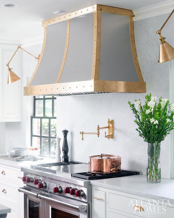 Brass swing arm kitchen wall sconces design ideas a french steel hood accented with brass studded straps is mounted between boston functional library wall lights to a white quartz backsplash above a brass aloadofball Image collections