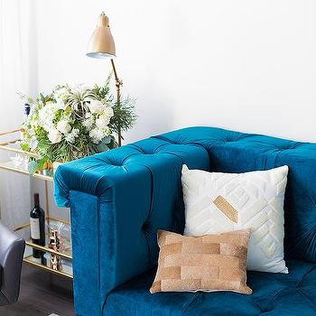 Gold Sunburst Mirror Over A Sapphire Blue Velvet Tufted