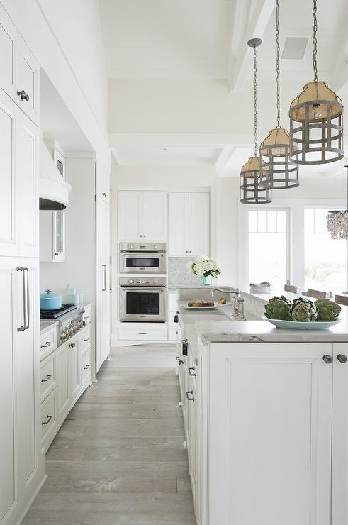 White Kitchen Oak Floor white beach style kitchen with gray wash oak wood floors - cottage