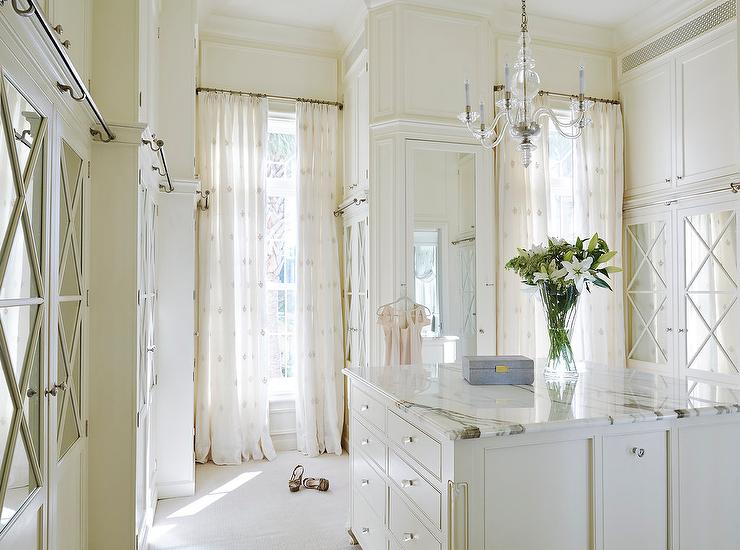 White And Ivory Walk In Closet Features A Glass Chandelier George II Illuminating Marble Top Island Adorned With Knobs