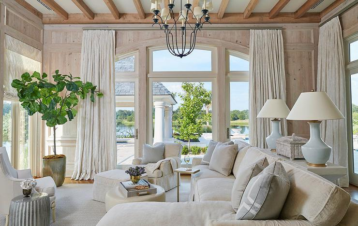 White And Tan Living Room Features An Iron Chandelier Illuminating A White  Sofa Table Topped With Powder Blue Lamps Situated Behind A Tan Skirted Sofa  With ... Part 65