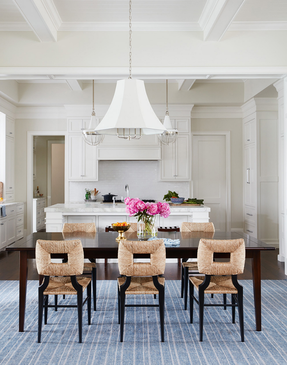 D A White Pleated Chandelier Illuminates A Mahogany Stained Rectangular Dining  Table Lined With Seagrass Chairs Placed Atop Denim Blue Striped Rug