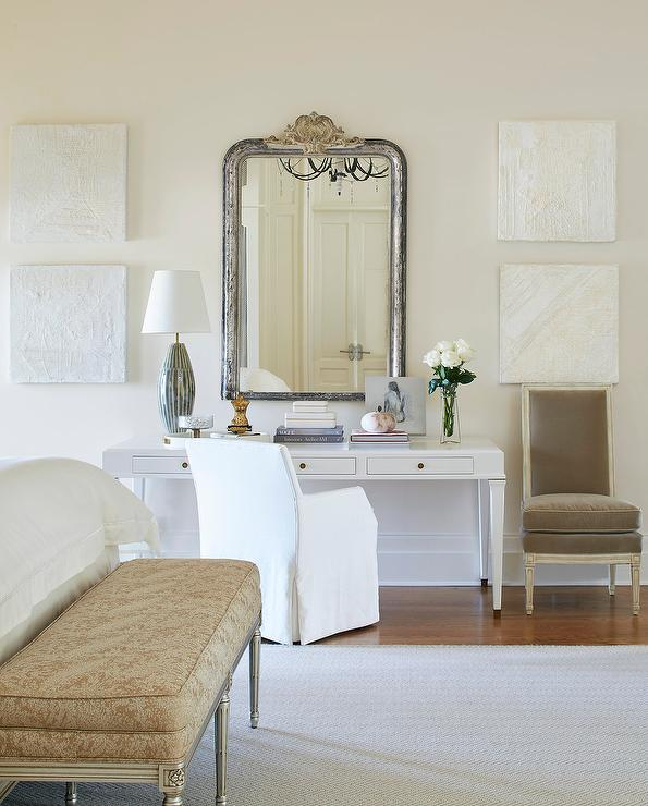 chic french bedroom features a white makeup vanity and desk paired with a white slipcovered chair placed under a distressed silver mirror flanked by white