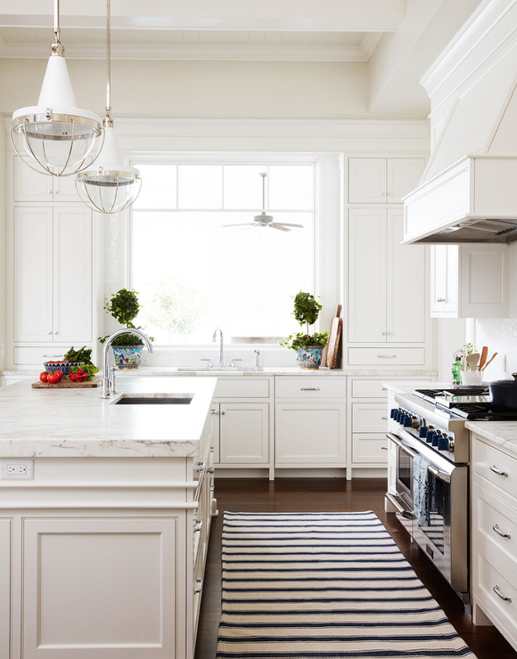 Two White Vintage Lanterns Illuminate A White Wainscoted Kitchen Island  Fitted With A Sink And Gooseneck Faucet.