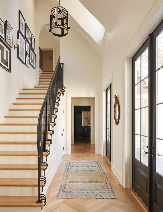 A sloped ceiling with skylight illuminates a foyer filled with a vintage  blue rug placed atop a blond wood herringbone pattern floor placed before a  row of ...