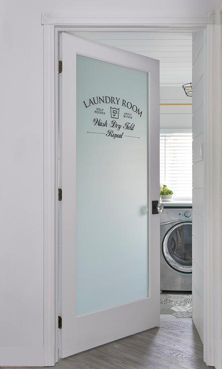 A Frosted Glass Etched Door Opens To A Laundry Room Fitted With Diagonal  Wood Floors, A White Shiplap Ceiling, And A Silver Front Loading Washer And  Dryer ...