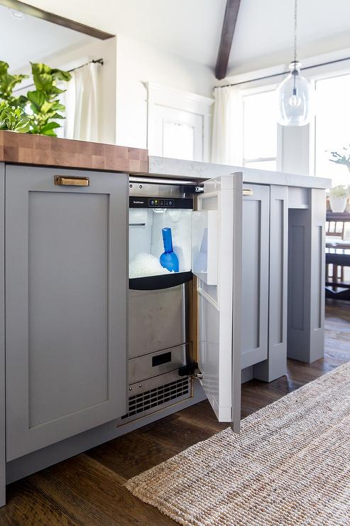 A Stainless Steel Ice Maker Is Concealed Behind Cabinet Door Of Gray Blue Kitchen Island Accented With Antique Brass Cup Pulls And Butcher Block Top