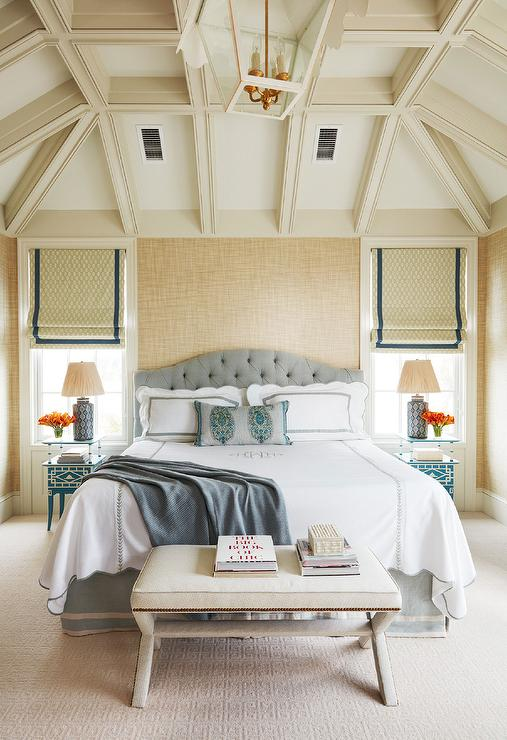 Chic bedroom features a vaulted ceiling with ivory wood beams accented with  a Coleen & Co The Tole Tent Lantern illuminating a steel gray tufted  headboard ...