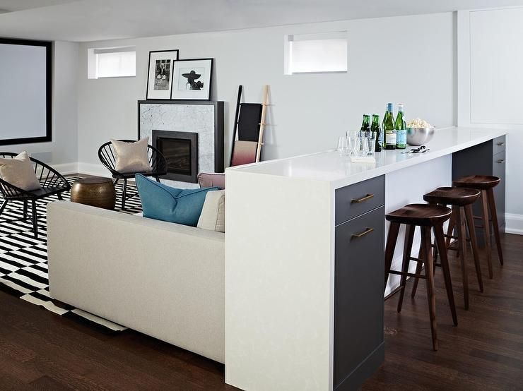 Chic Transitional Basement Boasts A White Quartz Waterfall Bar Fitted With Black Drawers And Seating Backless Wood Barstools Behind Light Gray Sofa