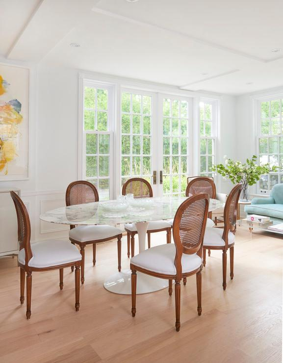 Chic Sparse Dining Room Boasts An Oval Marble Top Table Saarinen Surrounded By French Cane Chairs With Upholstered White