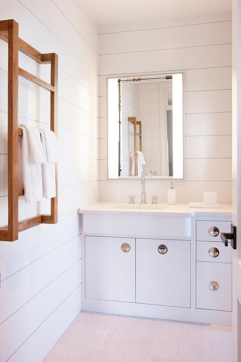 white cottage bathroom boasts white washstand adorned with large chrome hardware topped with a white corian countertop fitted with a jutted out sink and