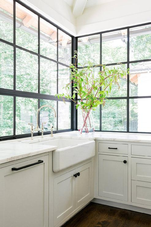 A Farmhouse Sink And Deck Mount Gooseneck Faucet Stands Under Black Framed  Factory Windows Surrounded By White Shaker Cabinets Adorned With Oil Rubbed  ...