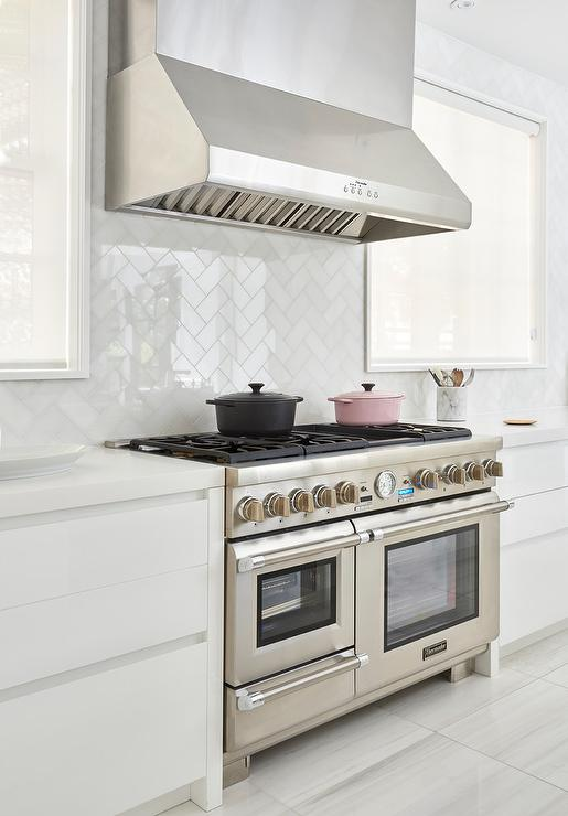 an elegant white kitchen separates hues with a thermador kitchen hood and stainless steel stove