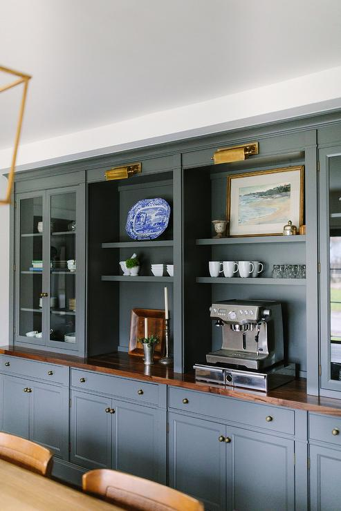 Chic Dining Space Features A Wall Of Dark Gray Built In Shelves Lined With An Espresso Machine Flanked By Glass Front Cabinets Stacked Over