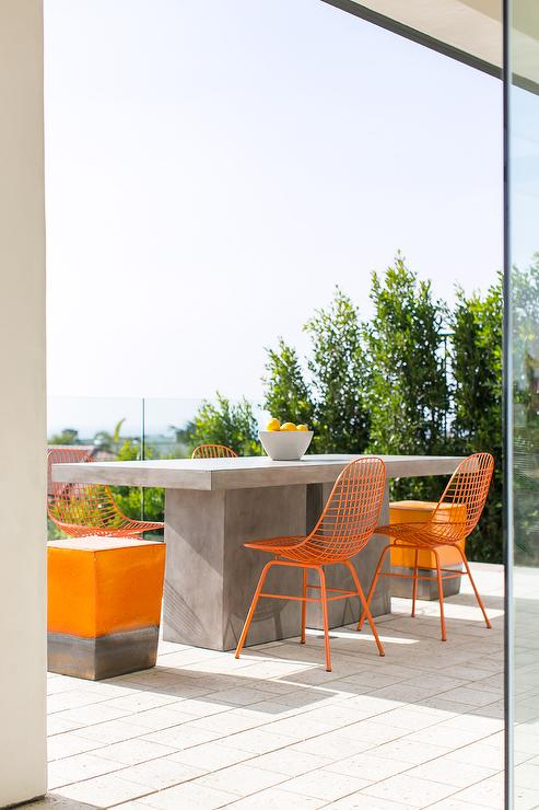 Concrete Block Outdoor Dining Table With Orange Metal Dining Chairs