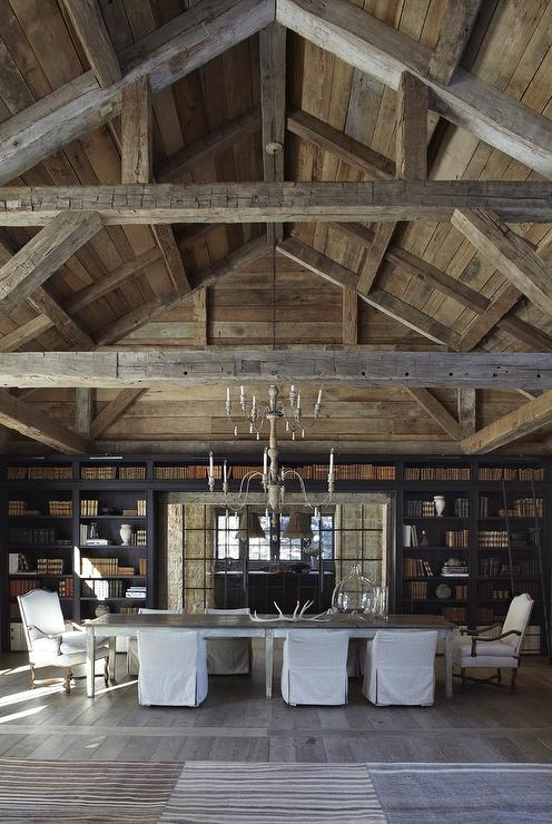 Stunning Country Cabin Dining Room Features Walls And A Vaulted Truss Ceiling Covered In Barn Board Lit By French Candle Chandeliers Hung Over Long