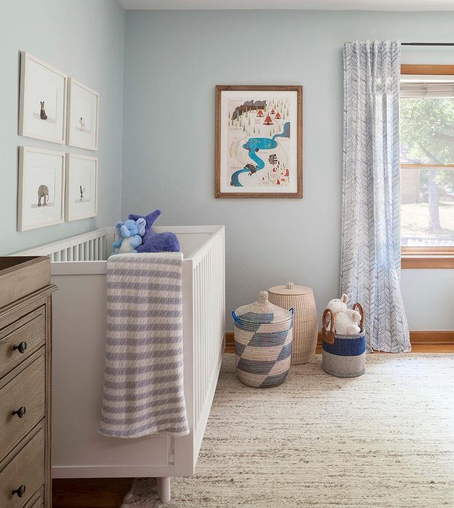 Charming Blue And White Nursery Features A Crib Placed On Gold Jute Rug Against Light Wall Beneath The Animal Print Prints