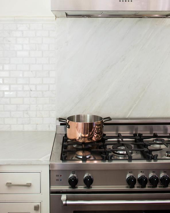 toned backsplash includes a white marble slab and whitegray subway tile that seemingly divides the counter space and the stainless steel cooktop stove