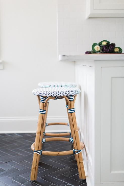 two serena u0026 lily riviera backless stools sit on black herringbone floor tiles in front of a white kitchen peninsula topped with a honed white marble