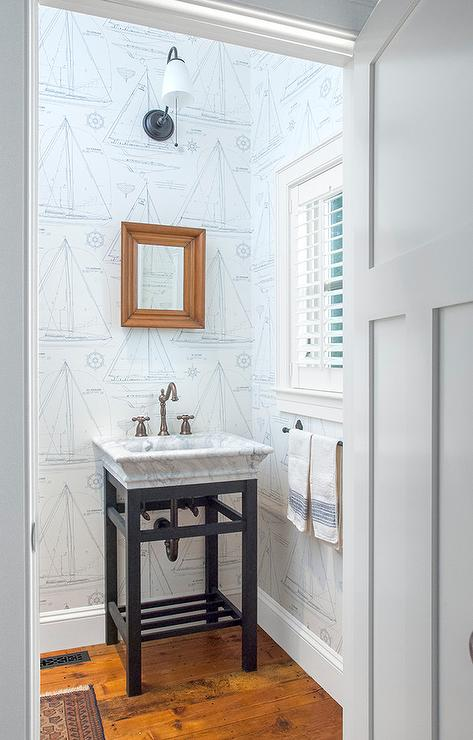 Clad in Ralph Lauren Chesapeake Wallpaper, this exquisite cottage kid's bathroom is lit by an oil rubbed bronze sconce mounted above an iron and marble ...