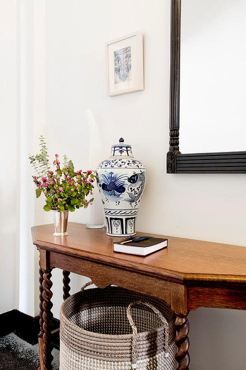 A Wood Foyer Table Accented With Rope Legs Sits Above A Gray Dip Dyed  Basket And Below A Black French Mirror Mounted To A White Wall.
