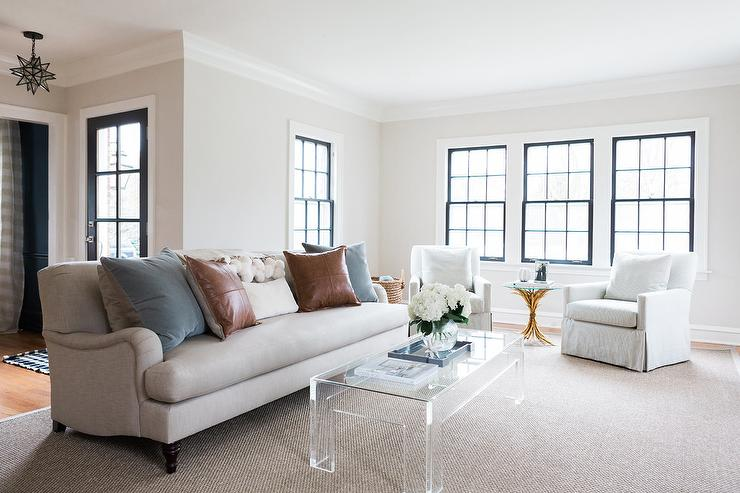 Sits On A Gray Bound Sisal Rug In Front Of An Ivory Sofa Complemented With Brown Leather And Slate Blue Pillows While Two Striped Accent Chairs