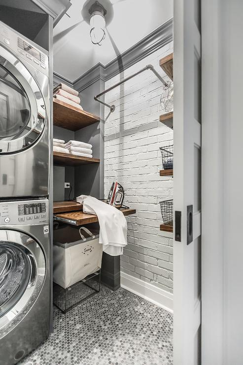 gray laundry room with pull out ironing table