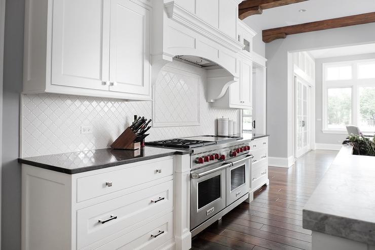between white shaker cabinets with polished nickel hardware and a black quatz countertop fixed against white arabesque backsplash tiles - Arabesque Tile Backsplash