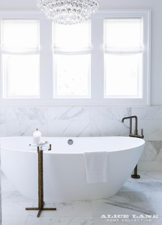 Restful Transitional Bathroom Boasts An Oval Freestanding Bathtub Paired  With An Angled Matte Black Tub Filler Mounted To White Marble Floor Tiles  And A ...