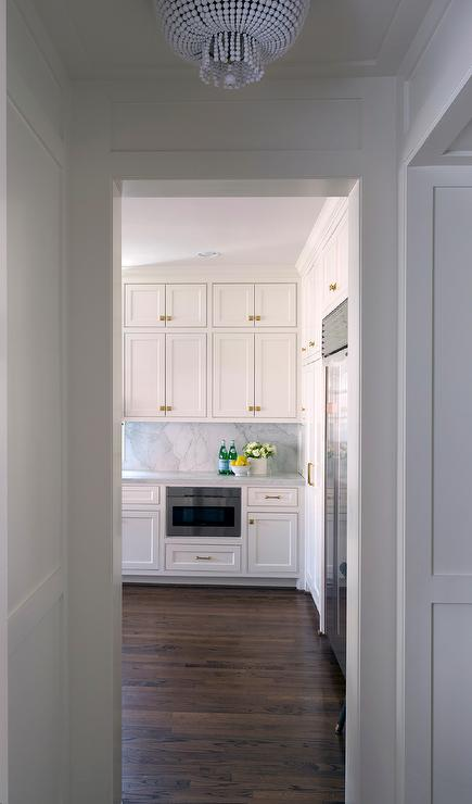 Stacked White Kitchen Cabinets With Brass Knobs