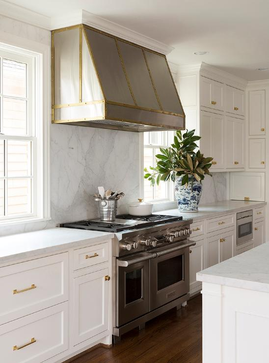 A Steel Hood Accented With A Brass Trim Is Fixed Between Windows To A Honed  White Marble Backsplash Above A Stainless Steel Dual Range Flanked By White  ...